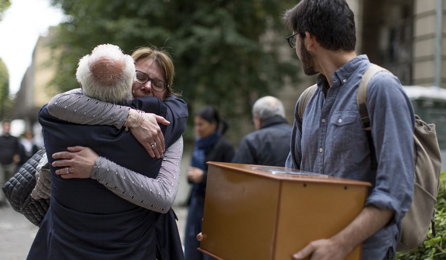 In this March 26, 2019 photo, Bonnie Loedel hugs her cousin while her brother Daniel Loedel holds a wooden urn containing the skeletal remains of their sister Isabel, as they arrive to the Remembrance, Truth and Justice Mausoleum for the Victims of State Sponsored Terrorism, at the public cemetery in La Plata, Argentina. Isabel Loedel, whose remains were only identified last year, was forcibly disappeared during the country's 1976-1983 dictatorship. (AP Photo/Tomas F. Cuesta)