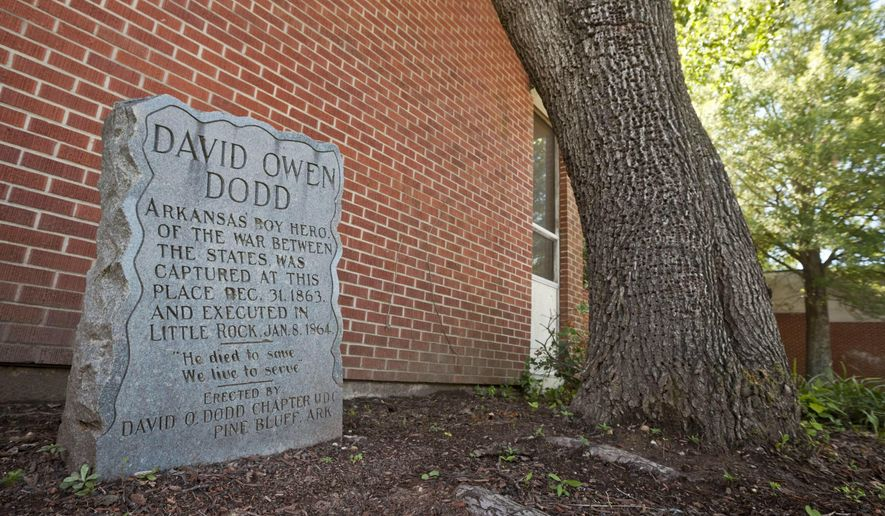 FILE - In this Sept. 18, 2012, file photo, a monument to teenage Confederate spy David O. Dodd, who was executed in 1864, is displayed in front of an elementary school named for him in Little Rock, Ark. Arkansas lawmakers are considering a bill that would make it illegal to remove or alter any military or historical monument on public property, including Confederate monuments, unless a state commission agrees to the changes. The Senate passed the bill 19-10 on Wednesday, April 3, 2019, but it has stalled in a House committee. (AP Photo/Danny Johnston File)