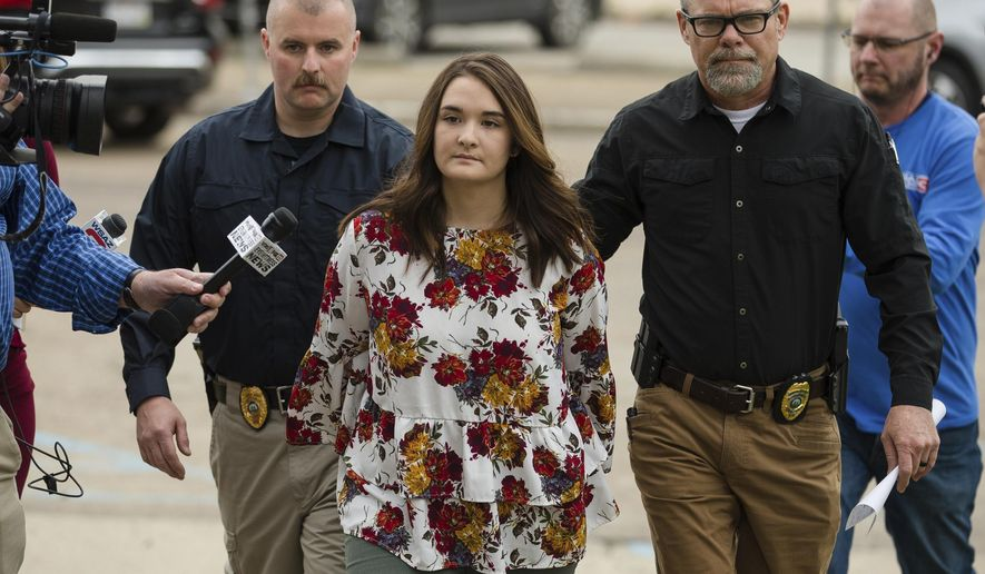 Santana Renee Adams is escorted into Cabell County Magistrate Court to be arraigned on charges for falsely reporting an emergency incident, Friday, April 5, 2019, in Huntington, W.Va. The charges stem from Adams falsely reporting that an Egyptian man attempted to kidnap her daughter from a West Virginia shopping mall Monday evening. (Sholten Singer/The Herald-Dispatch via AP)