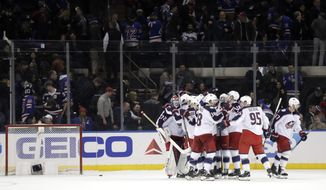 Columbus Blue Jackets swarm goaltender Sergei Bobrovsky, left, of Russia, after he made three saves during the shootout against the New York Rangers during an NHL hockey game Friday, April 5, 2019, in New York. The Blue Jackets won 3-2. (AP Photo/Julio Cortez)