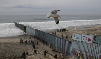 In this Dec. 10, 2018, file photo, people look on from the Mexican side, left, as U.S. Border Patrol agents on the other side of the U.S. border wall in San Diego prepare for the arrival of hundreds of pro-migration protestors, seen from Tijuana, Mexico. (AP Photo/Rebecca Blackwell, File) **FILE**