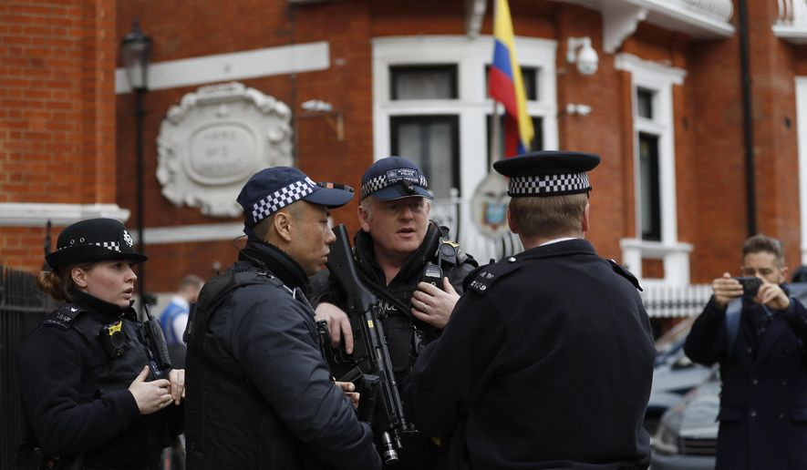 "Armed police arrive outside the Ecuadorian Embassy, in London, Friday, April 5, 2019, where Wikileaks founder Julian Assange has been holed up since 2012, as a van with a Free Assange placard had parked illegally on a diplomatic spot outside the Embassy. A senior Ecuadorian official said no decision has been made to expel Julian Assange from the country's London embassy despite tweets from Wikileaks that sources had told it he could be kicked out within ""hours to days"" on Friday. (AP Photo/Alastair Grant)"