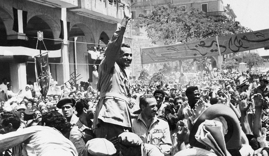 FILE - In this June 18, 1956 file photo, Egyptian leader Gamal Abdel Nasser waves as he moves through Port Said, Egypt, during a ceremony in which Egypt formally took over control of the Suez Canal from Britain. The ensuing conflict arguably marked the biggest crisis of British diplomacy in postwar period until the current crisis relating to the country's struggles to leave the European Union. (AP Photo/File)