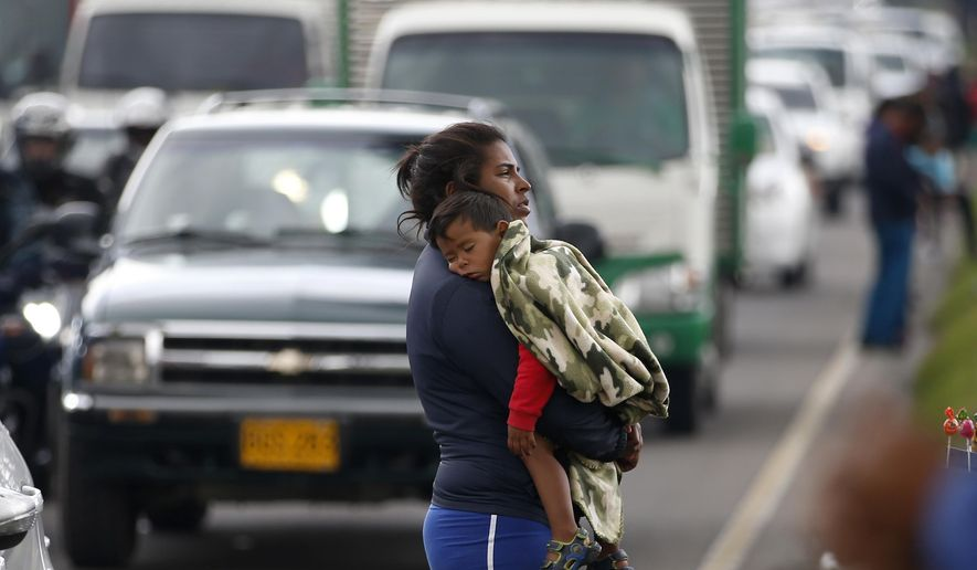 A Venezuelan migrant waits for traffic to come to a standstill so that she can ask drivers for spare change, in Bogota, Colombia, Thursday, April 4, 2019. According to U.N. children's agency UNICEF, as a result of the Venezuela migrant crisis, 1.1 million children will need help across Latin America and the Caribbean in 2019. (AP Photo/Fernando Vergara)