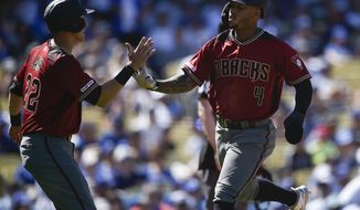 Arizona Diamondbacks' Ketel Marte, right, celebrates with Jake Lamb after both scoring off a two-run double by Nick Ahmed during the fourth inning of an MLB baseball game against the Los Angeles Dodgers in Los Angeles, Sunday, March 31, 2019. (AP Photo/Kelvin Kuo)