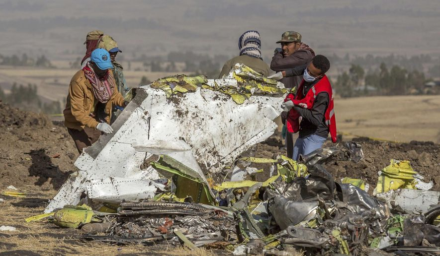 FILE - In this Monday, March 11, 2019 file photo, rescuers work at the scene of an Ethiopian Airlines flight crash near Bishoftu, or Debre Zeit, south of Addis Ababa, Ethiopia. Pilots of the Ethiopian Airlines flight encountered problems with their new Boeing jetliner from nearly the moment they roared down the runway and took off. Ethiopian authorities issued a preliminary report Thursday, April 4, 2019, on the March 10 crash. (AP Photo/Mulugeta Ayene, File)