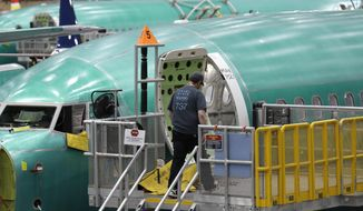 FILE- In this March 27, 2019, file photo a Boeing 737 MAX 8 airplane is shown on the assembly line during a brief media tour of Boeing's 737 assembly facility in Renton, Wash. Boeing is under investigation on multiple fronts. The Justice Department is looking into possible criminal violations involving certification that the 737 Max introduced in 2017 was safe. Congressional committees are also investigating the crashes and questioning a program under which the FAA delegates many safety checks for planes to Boeing and other manufacturers to save money. (AP Photo/Ted S. Warren, File)