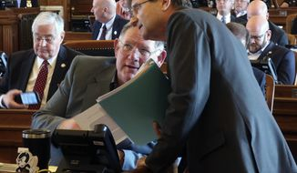 Kansas House Insurance Committee Chairman Jene Vickrey, right, R-Louisburg, confers with Majority Leader Dan Hawkins, R-Wichita, during a debate on an insurance bill sought by the Kansas Farm Bureau, Friday, April 5, 2019, at the Statehouse in Topeka, Kan. Lawmakers have approved the bill, which allows the Farm Bureau to sell health coverage to its members that doesn't comply with federal mandates. (AP Photo/John Hanna)