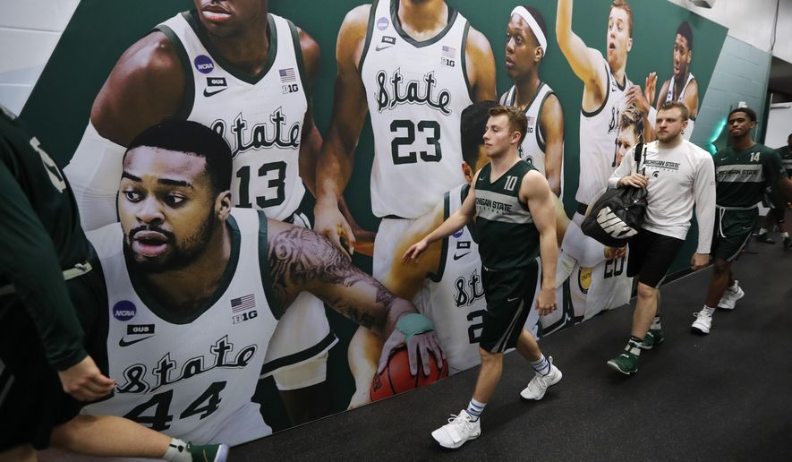 Michigan State guard Jack Hoiberg walks to the court for a practice session for the semifinals of the Final Four NCAA college basketball tournament, Friday, April 5, 2019, in Minneapolis. (AP Photo/Charlie Neibergall)