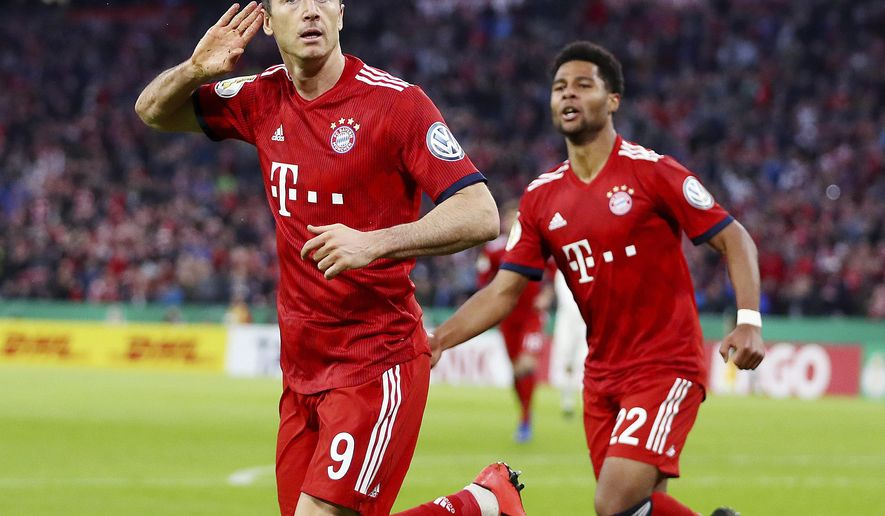 Munich's Robert Lewandowski,left, celebrates his side's third goal during the German Soccer Cup match between FC Bayern Munich and 1. FC Heidenheim in Munich, Germany, Wednesday, April 3, 2019. (AP Photo/Matthias Schrader)