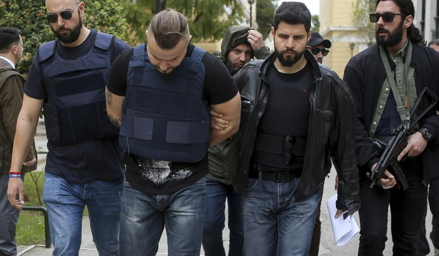 Plain clothed policemen escort a Bulgarian man, center, at a court in Athens, Friday, April 5, 2019. Greek authorities said Friday they have arrested and charged a Bulgarian man over the suspected contract killing of a Greek-Australian who was fatally shot outside his home in an Athens seaside suburb last year. (Dimitris Kapadais/InTime News via AP)