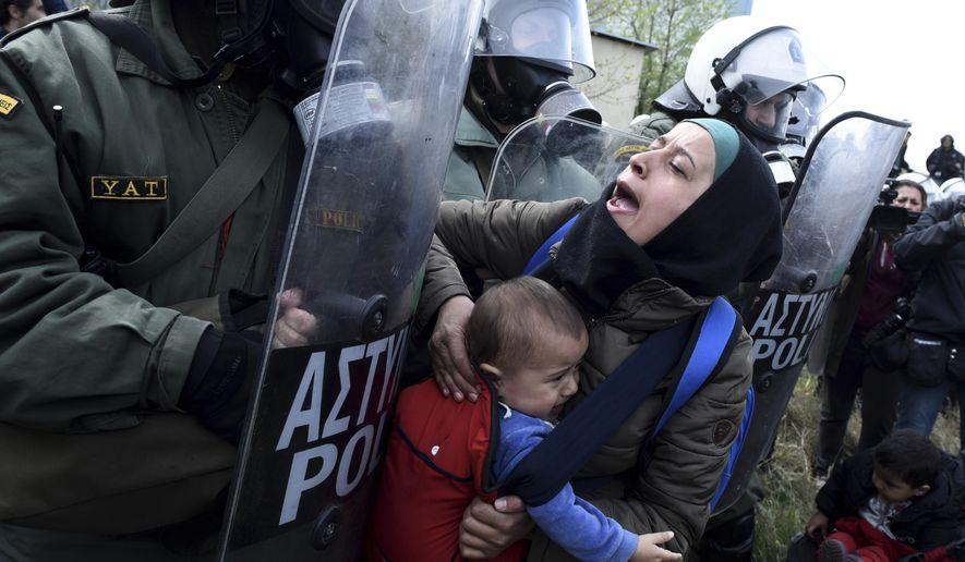 A migrant woman with a child pushing with riot police outside a refugee camp in the village of Diavata, west of Thessaloniki, northern Greece, Friday, April 5, 2019. Clashes broke out Thursday between migrants and Greek police outside a camp in northern Greece, where hundreds gathered in the hope of reviving a route that saw hundreds of thousands enter more prosperous countries in Europe. (AP Photo/Giannis Papanikos)