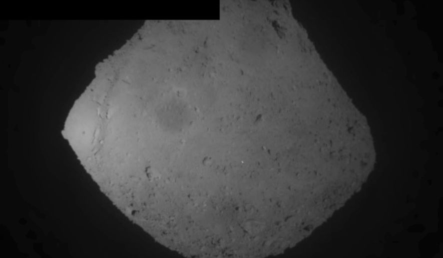 This image released by the Japan Aerospace Exploration Agency (JAXA) shows the asteroid Ryugu Friday, April 5, 2019. Japan's space agency JAXA said its Hayabusa2 spacecraft released an explosive onto the asteroid to make a crater on its surface and collect underground samples to find possible clues to the origin of the solar system. Friday's mission is the riskiest for Hayabusa2, as it has to immediately get away so it won't get hit by flying shards from the blast. (JAXA via AP)