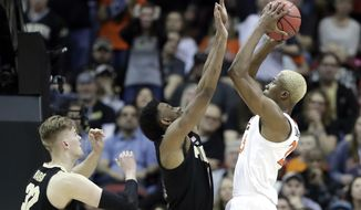 Virginia's Mamadi Diakite shoots over Purdue's Aaron Wheeler, center, and Matt Haarms (32) during the second half of the men's NCAA Tournament college basketball South Regional final game, Saturday, March 30, 2019, in Louisville, Ky. (AP Photo/Michael Conroy)