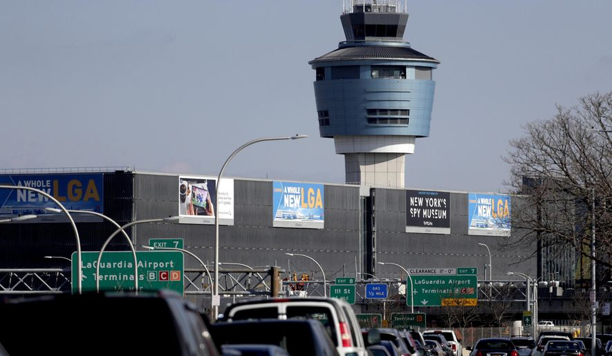 FILE - This Friday, Jan. 25, 2019 file photo shows the air traffic control tower at LaGuardia Airport in New York. On Friday, April 5, 2019, The Associated Press has found that stories circulating on the internet that the minimum wage of $19 at the facility has resulted in $7 croissants, are untrue. The minimum wage there is currently $13.60 an hour. (AP Photo/Julio Cortez)