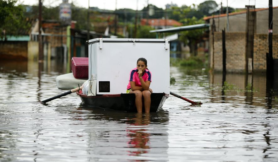 Carolina Vera, 13, rides on a boat through a flooded street in the Villa Colorada neighborhood, in Asuncion, Paraguay, Friday, April 5, 2019. More than 20,000 people in Paraguay have been evacuated after torrential rains caused extensive flooding. (AP Photo/Jorge Saenz)
