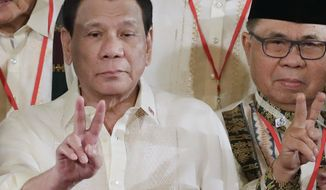 FILE - In this Friday, Feb. 22, 2019, file photo, Philippine President Rodrigo Duterte, left, and Moro Islamic Liberation Front chairman Murad Ebrahim, right, flash peace signs following oath-taking ceremony for the creation of the Bangsamoro Transition Authority (BTA) at the Presidential Palace in Manila, Philippines.  The Philippine president has warned he would declare a revolutionary government and arrest his detractors and outlaws if he says he's pushed to the wall. President Rodrigo Duterte made the threat late Thursday, April 4, in a speech where he expressed his exasperation with criticism even while he's trying to fight irregularities.(AP Photo/Bullit Marquez, File)