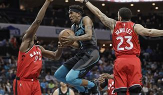 Charlotte Hornets' Malik Monk (1) drives between Toronto Raptors' Fred VanVleet (23) and Serge Ibaka (9) during the first half of an NBA basketball game in Charlotte, N.C., Friday, April 5, 2019. (AP Photo/Chuck Burton)