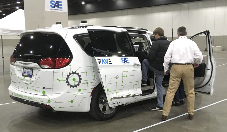 A person gets into a self-driving Chrysler Pacifica Hybrid Friday, April 5, 2019, in Detroit. Hundreds from the general public are signed up for the six-minute journey that leads riders through a course set up inside a Detroit convention center, as part of an effort to clear up misunderstandings and confusion about the technology. (AP Photo/Mike Householder)