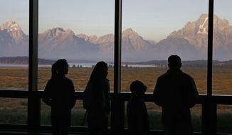 FILE - In this Aug. 28, 2016 file photo, visitors watch the morning sun illuminate the Grand Tetons from within the Great Room at the Jackson Lake Lodge, in Grand Teton National Park, north of Jackson Hole, Wyo. Scientists have completed the most detailed map yet of the geologic fault at the foot of the Teton Range, one of the most visually striking and potentially dangerous seismic areas in North America. (AP Photo/Brennan Linsley, File)