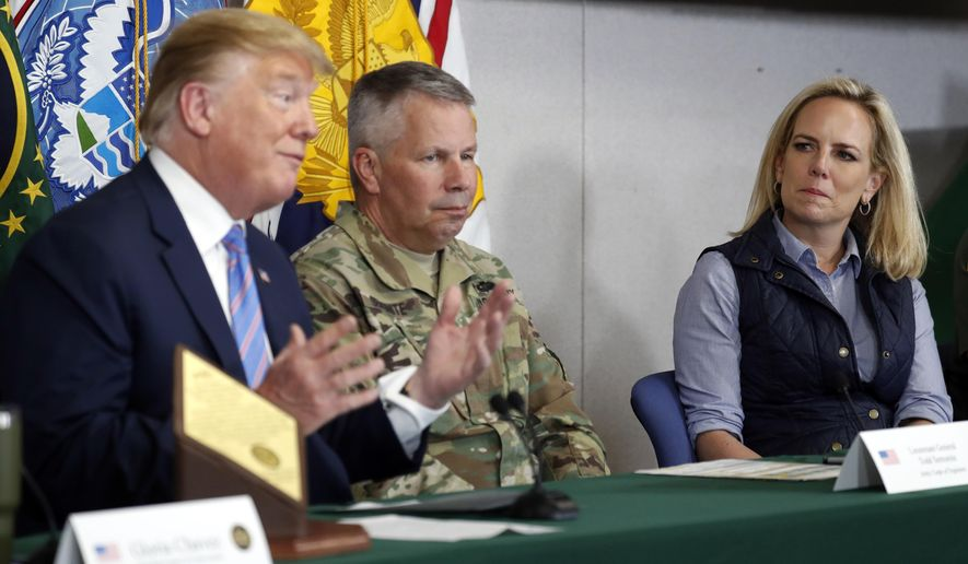 Lt. Gen. Todd Semonite, commanding General of the U.S. Army corps of Engineers , center and Homeland Security Secretary Kirstjen Nielsen, listens as President Donald Trump participates in a roundtable on immigration and border security at the U.S. Border Patrol Calexico Station in Calexico, Calif., Friday April 5, 2019. Trump headed to the border with Mexico to make a renewed push for border security as a central campaign issue for his 2020 re-election. (AP Photo/Jacquelyn Martin)