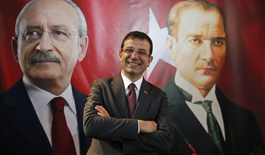 Backdropped by a poster of Kemal Kilicdaroglu, left, the main opposition Republican People's Party (CHP) leader, and modern Turkey's founder Mustafa Kemal Ataturk, right, Ekrem Imamoglu, the CHP's mayoral candidate in Istanbul, poses for The Associated Press following an interview in Istanbul, Thursday, April 4, 2019. Imamoglu said he's confident that the result of a recount of votes in the city will confirm his victory and has renewed an appeal to Turkey's President Recep Tayyip Erdogan to help end the standoff. Imamoglu won the tight race for Istanbul in Sunday's local elections in a major upset for Erdogan, who rose to power as the mayor of the city of 15 million and has said that whoever wins Istanbul wins to whole of Turkey. (AP Photo/Lefteris Pitarakis)