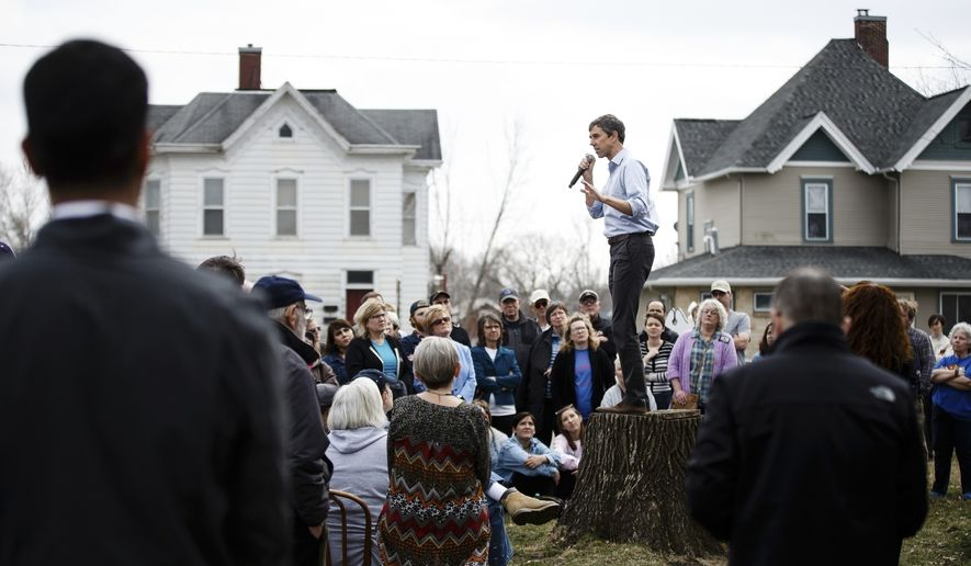 In this Friday, April 5, 2019 photo, people listen as Democratic presidential candidate and former Texas Representative Beto O'Rourke stands on a stump to give his speech at the Mowry Irvine Mansion during a swing though Iowa in Marshalltown, Iowa. (Brian Powers/The Des Moines Register via AP)