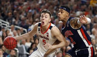 Virginia's Kyle Guy (5) drives against Auburn's Bryce Brown (2) during the first half in the semifinals of the Final Four NCAA college basketball tournament, Saturday, April 6, 2019, in Minneapolis. (AP Photo/Jeff Roberson) **FILE**