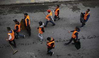 In this Friday March 22, 2019 image, groups of young people roam the streets picking up bottles and other detritus after Algeria's weekly pro-democracy protests, in a powerful demonstration of the movement's peaceful, hopeful spirit. (AP Photo/Fateh Guidoum)