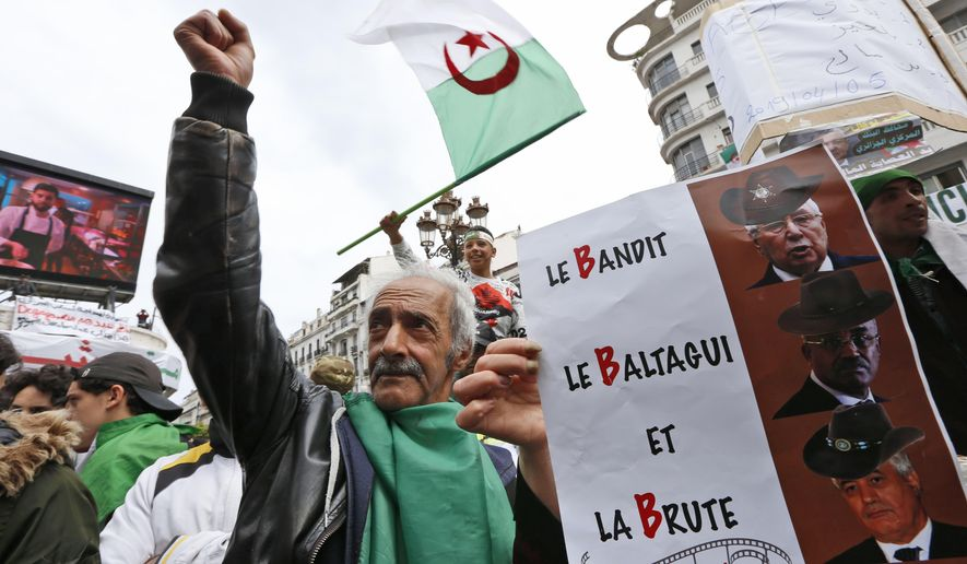 A demonstrator holds a sign referring to the three B's, Abdelkader Bensalah, Tayeb Belaiz et Noureddine Bedoui, interim rulers they want removed from their posts, during a rally in Algiers, Friday April 5, 2019. Thousands of Algerians are chanting, singing and cheering after their movement forced out longtime President Abdelaziz Bouteflika - and demanding that other top figures leave too. Crowds massed Friday in Algiers boulevards and headed toward the central post office, symbol of the movement that has upended this energy-rich North African country. (AP Photo/Toufik Doudou)