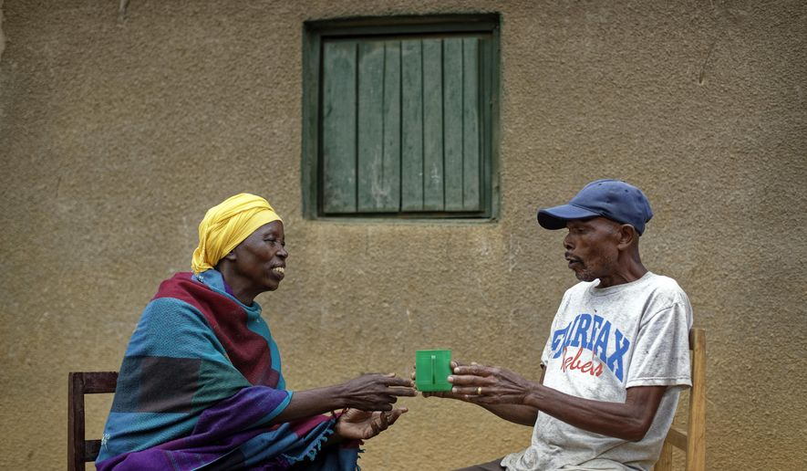 "In this photo taken Thursday, April 4, 2019, genocide survivor Laurencia Mukalemera, left, a Tutsi, is offered a cup of water by Tasian Nkundiye, right, a Hutu who murdered her husband and spent eight years in prison for the killing and other crimes, before being interviewed at Nkundiye's home in the reconciliation village of Mbyo, near Nyamata, in Rwanda. Twenty-five years after the genocide the country has six ""reconciliation villages"" where convicted perpetrators who have been released from prison after publicly apologizing for their crimes live side by side with genocide survivors who have professed forgiveness. (AP Photo/Ben Curtis)"