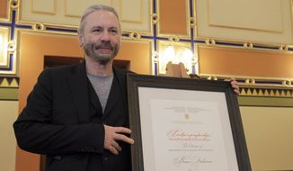 Bruce Dickinson poses for cameras with his honorary citizen certificate at the city hall in Sarajevo, Bosnia-Herzegovina, Saturday, April 6, 2019. Bosnia's capital Sarajevo has declared Iron Maiden lead singer Bruce Dickinson an honorary citizen in gratitude for the concert the heavy metal band held while the city was under siege during 1992-95 war. (AP Photo/Eldar Emric)