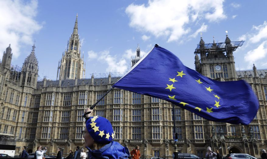 FILE - In this March 25, 2019, file photo, an anti-Brexit campaigner shows her support for Europe waving a European Union flag outside Parliament in London. Britain is set to leave the EU on April 12 without a Brexit agreement in place unless a plan is reached or the EU grants an extension. (AP Photo/Kirsty Wigglesworth, File)