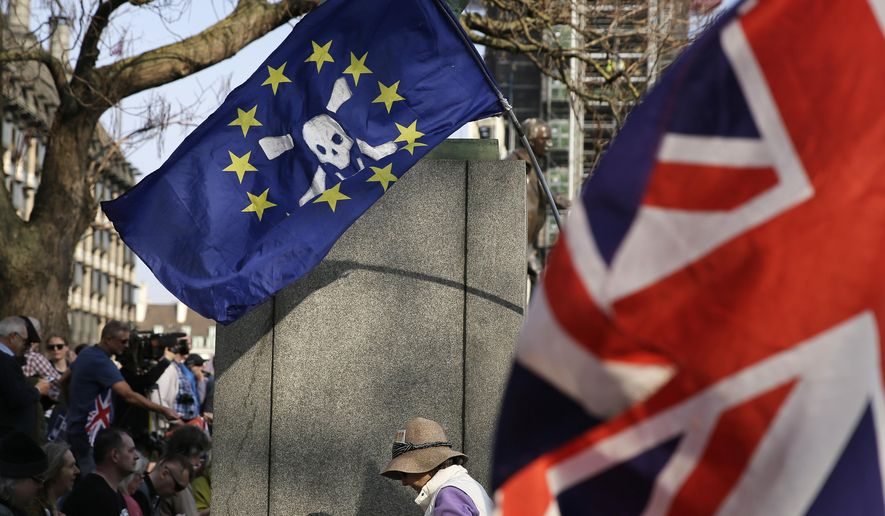 """FILE - In this March 29, 2019, file photo, Pro-Brexit leave the European Union supporters wave flags in Parliament Square at the end of the final leg of the """"March to Leave"""" in London. Britain is set to leave the EU on April 12 without a Brexit agreement in place unless a plan is reached or the EU grants an extension. (AP Photo/Matt Dunham, File)"""