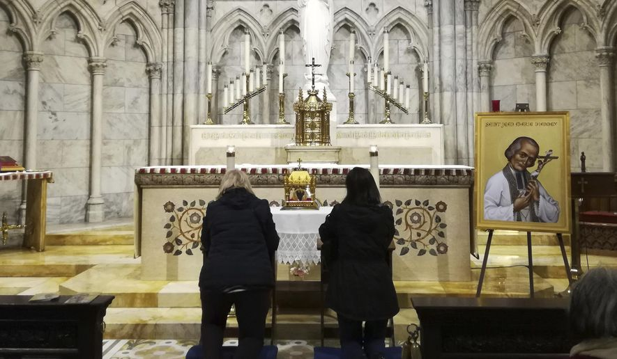 Two women pray in front a container bearing the heart of St. John Vianney Saturday, April 6, 2019 at St. Patrick's Cathedral in New York. The 150-year-old heart of the French priest is being toured throughout the United States. The tradition of venerating the body parts of saintly Catholics goes back to the Middle Ages in Italy. (AP Photo/Julie Walker)