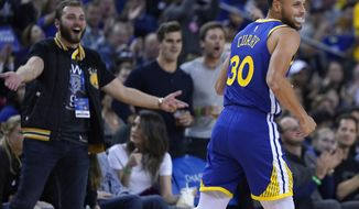 Golden State Warriors guard Stephen Curry (30) smiles after making a 3 point shot against the Cleveland Cavaliers during the second half of an NBA basketball game Friday, April 5, 2019, in Oakland, Calif. (AP Photo/Tony Avelar)