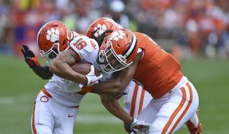 Clemson's T.J. Chase (18) is tackled by Shaq Smith, right, and Denzel Johnson, back, during Clemson's annual Orange and White NCAA college football spring scrimmage Saturday, April 6, 2019, in Clemson, S.C. (AP Photo/Richard Shiro) **FILE**