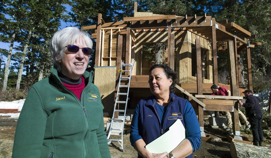 In this Thursday, March 28, 2019 photo, Juneau Raptor Center board members Janet Capito, left, and Dale Cotton talk about construction on a new education display on Mount Roberts in Juneau, Alaska. The display will house Lady Baltimore, an adult bald eagle that is not releasable back to the wild. (Michael Penn/The Juneau Empire via AP)