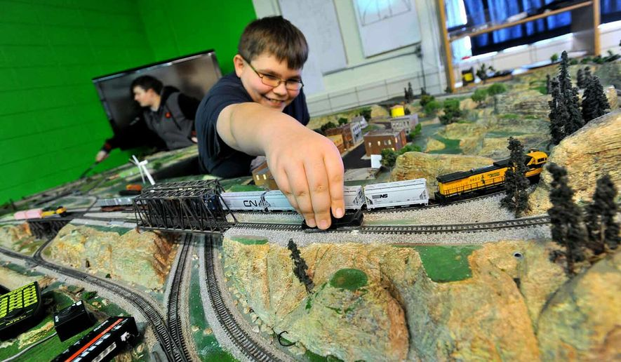 In this March 29, 2019, photo, Southeast Valley Middle School train club member Nykolas Albrecht, 11, cleans a section of track on their layout as fellow club member Emilie High, 13, left, works on another section in Burnside, Iowa. Students in the school operate a model railroad that's part of its model train club. (Hans Madsen/The Messenger via AP)