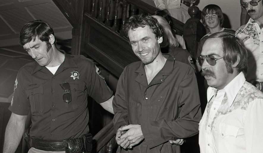 FILE - In this 1977 file photo, serial killer Ted Bundy, center, is escorted out of court at the Pitkin County courthouse, in Aspen, Colorado. He was accused of killing a woman in Snowmass Village in January 1975. Prosecutors have held onto nine boxes of evidence and other material related to the case and are in the process of digitizing the items. (Ross Dolan/Glenwood Springs Post Independent via AP, File)