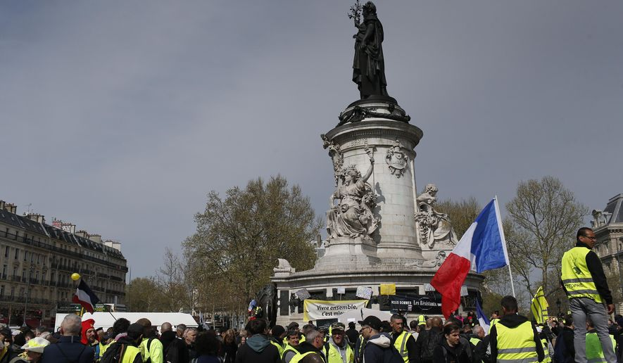 Yellow wests protesters rally in Paris, France, Saturday, April 6, 2019. The demonstrators are undeterred by protest bans or repeated injuries in 21 weeks of demonstrations, marching again Saturday in Paris and other cities to keep pressing President Emmanuel Macron to do more to help working classes, redesign French politics or step down altogether. (AP Photo/Rafael Yaghobzadeh)