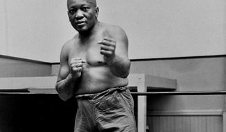 FILE - In this 1932 file photo, boxer Jack Johnson, the first black world heavyweight champion, poses in New York City.  A Texas Gulf Coast home where Johnson once lived has been heavily damaged in a fire.The blaze caused a wall to collapse in the vacant home Friday, April 5, 2019 in Galveston, Texas. Fire Chief Mike Wisko said that the building was in the process of being renovated. (AP Photo/File)