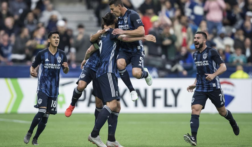 LA Galaxy's Uriel Antuna, Jonathan dos Santos, back, Zlatan Ibrahimovic, Daniel Steres and Romain Alessandrini, from left, celebrate Ibrahimovic's goal against the Vancouver Whitecaps during the second half of an MLS soccer match Friday, April 5, 2019, in Vancouver, British Columbia. (Darryl Dyck/The Canadian Press via AP)