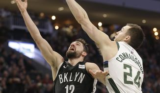Brooklyn Nets' Joe Harris, left, shoots against the Milwaukee Bucks' Pat Connaughton, right, during the second half of an NBA basketball game Saturday, April 6, 2019, in Milwaukee. (AP Photo/Jeffrey Phelps)