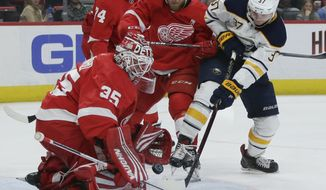 Detroit Red Wings goaltender Jimmy Howard (35) stops a shot on goal by Buffalo Sabres center Casey Mittelstadt (37) with Detroit Red Wings defenseman Joe Hicketts (2) helping defend the goal during the first period of an NHL hockey game Saturday, April 6, 2019, in Detroit. (AP Photo/Duane Burleson)