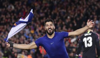 Barcelona forward Luis Suarez waves with his shirt as he celebrates scoring his side's first goal after passing Atletico goalkeeper Jan Oblak, right, during a Spanish La Liga soccer match between FC Barcelona and Atletico Madrid at the Camp Nou stadium in Barcelona, Spain, Saturday April 6, 2019. (AP Photo/Manu Fernandez)