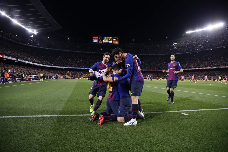 Barcelona players hug teammate Luis Suarez after he scores his side's first goal during a Spanish La Liga soccer match between FC Barcelona and Atletico Madrid at the Camp Nou stadium in Barcelona, Spain, Saturday April 6, 2019. (AP Photo/Manu Fernandez)
