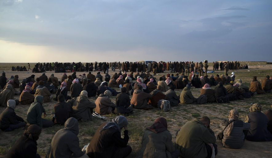 """FILE - In this Friday, Feb. 22, 2019 file photo, Men, foreground, women and children wait to be screened by U.S.-backed Syrian Democratic Forces (SDF) fighters after being evacuated out of the last territory held by Islamic State militants, near Baghouz, eastern Syria. The U.S.-led coalition says it has supported its Kurdish-led Syrian allies during an """"incident"""" in a prison in northeastern Syria where Islamic State militants attempted to escape. (AP Photo/Felipe Dana, File)"""