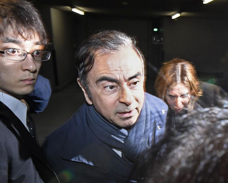 In this Wednesday, April 3, 2019, file photo, former Nissan Chairman Carlos Ghosn, center, leaves his lawyer's office in Tokyo. Tokyo prosecutors arrested Ghosn on Thursday, April 4, 2019 for a fourth time on fresh allegations that cut short his brief time outside detention. (Sadayuki Goto/Kyodo News via AP, File)