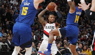 Portland Trail Blazers guard Damian Lillard, rear, looks to pass the ball as Denver Nuggets center Nikola Jokic, left, and guard Gary Harris defend during the second half of an NBA basketball game Friday, April 5, 2019, in Denver. The Nuggets won 119-110. (AP Photo/David Zalubowski)
